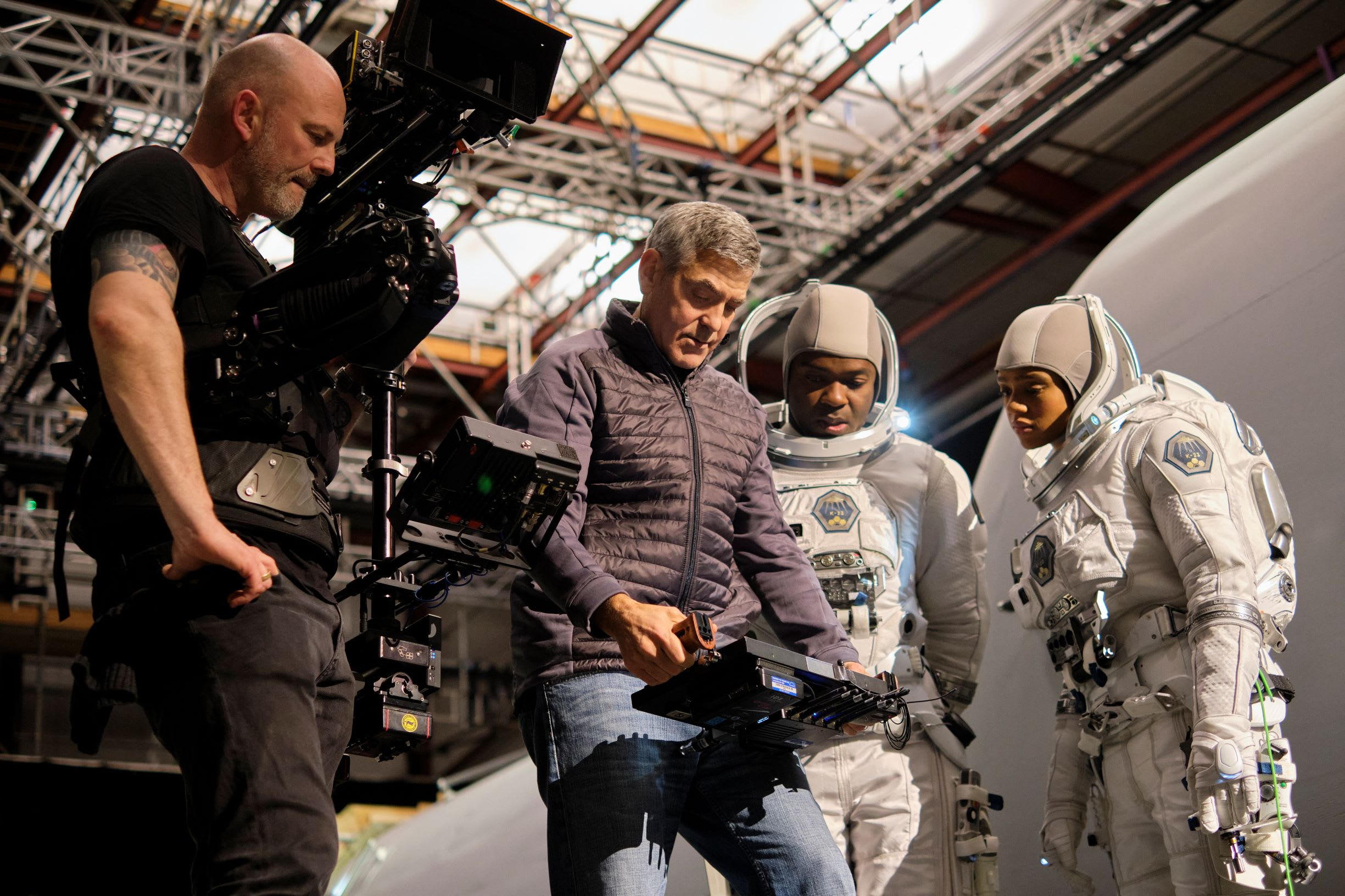 George Clooney pictured looking at an electronic device while standing next to two people dressed in astronaut costumes and another dressed all in black