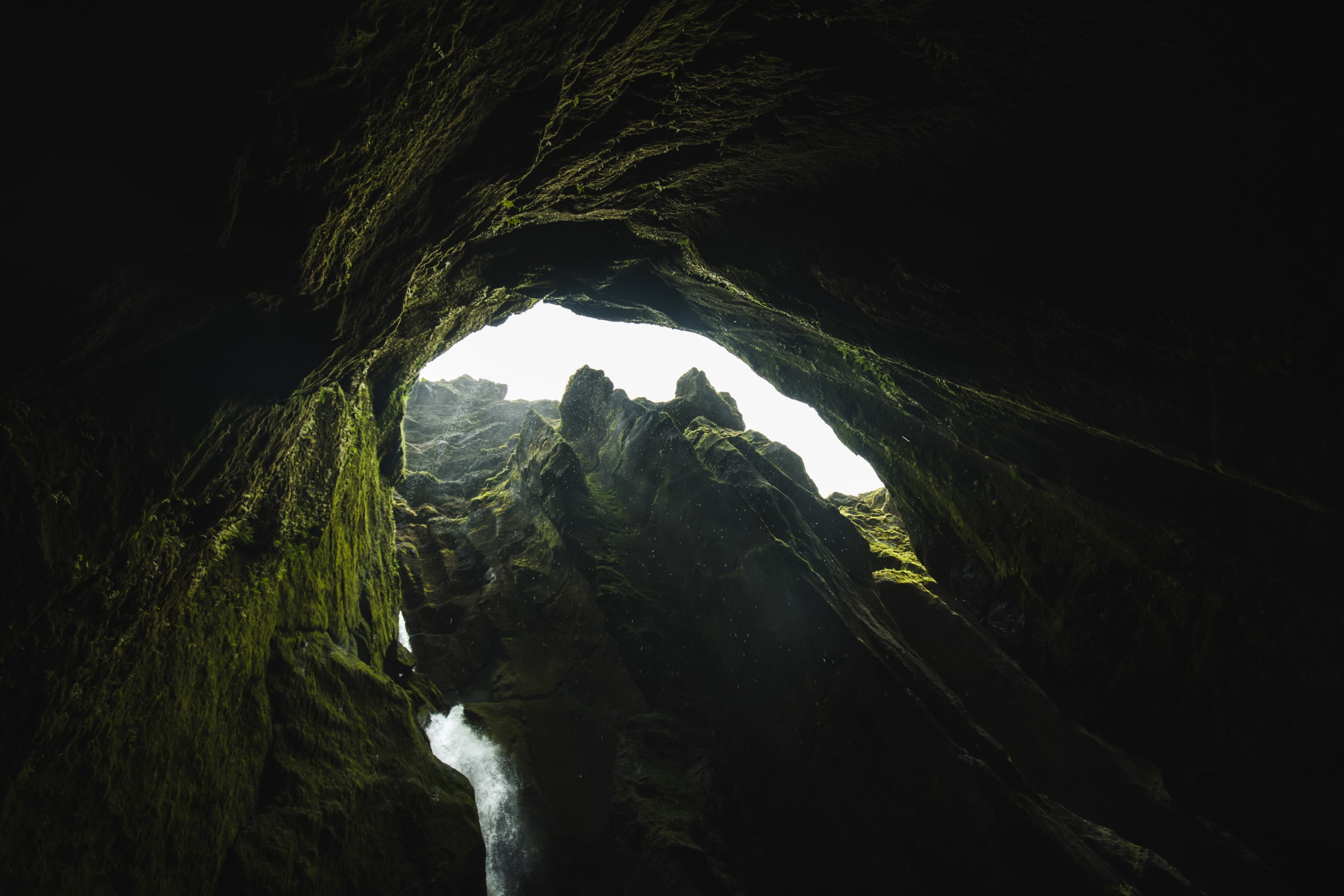 A view from within a cave-like structure with a small body of water in the foreground, looking out towards the light
