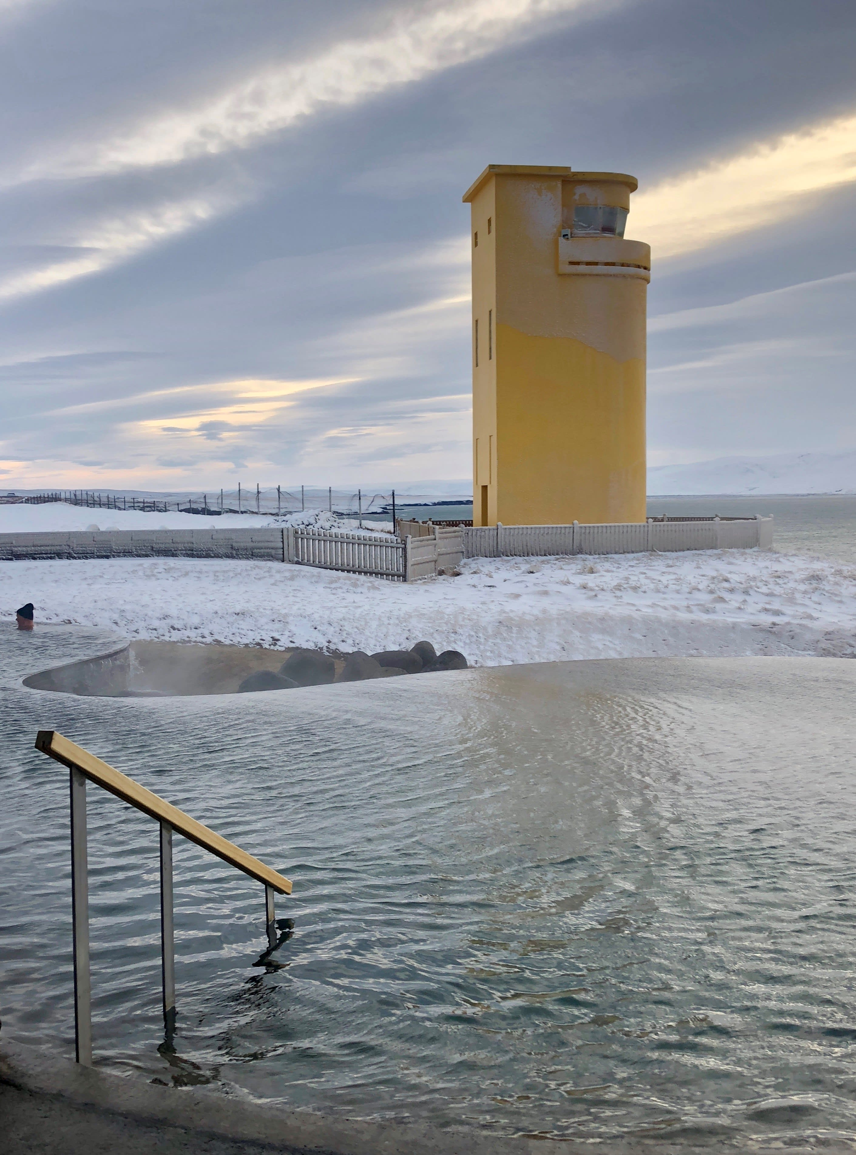 The GeoSea geothermal baths look out on to the sea, where a yellow lighthouse can be seen