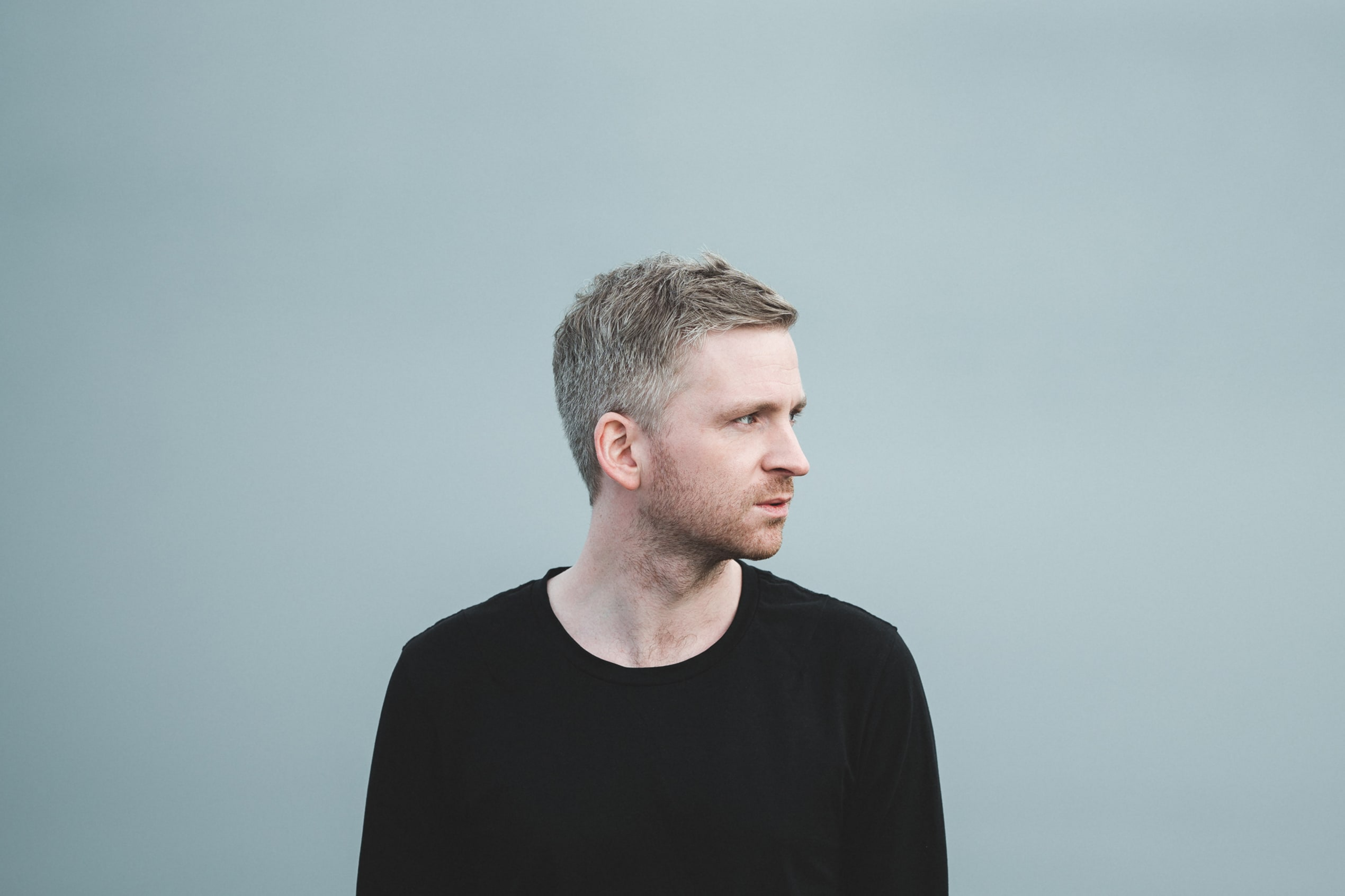 Olafur Arnalds pictured in a black sweater, with his head facing off to the side