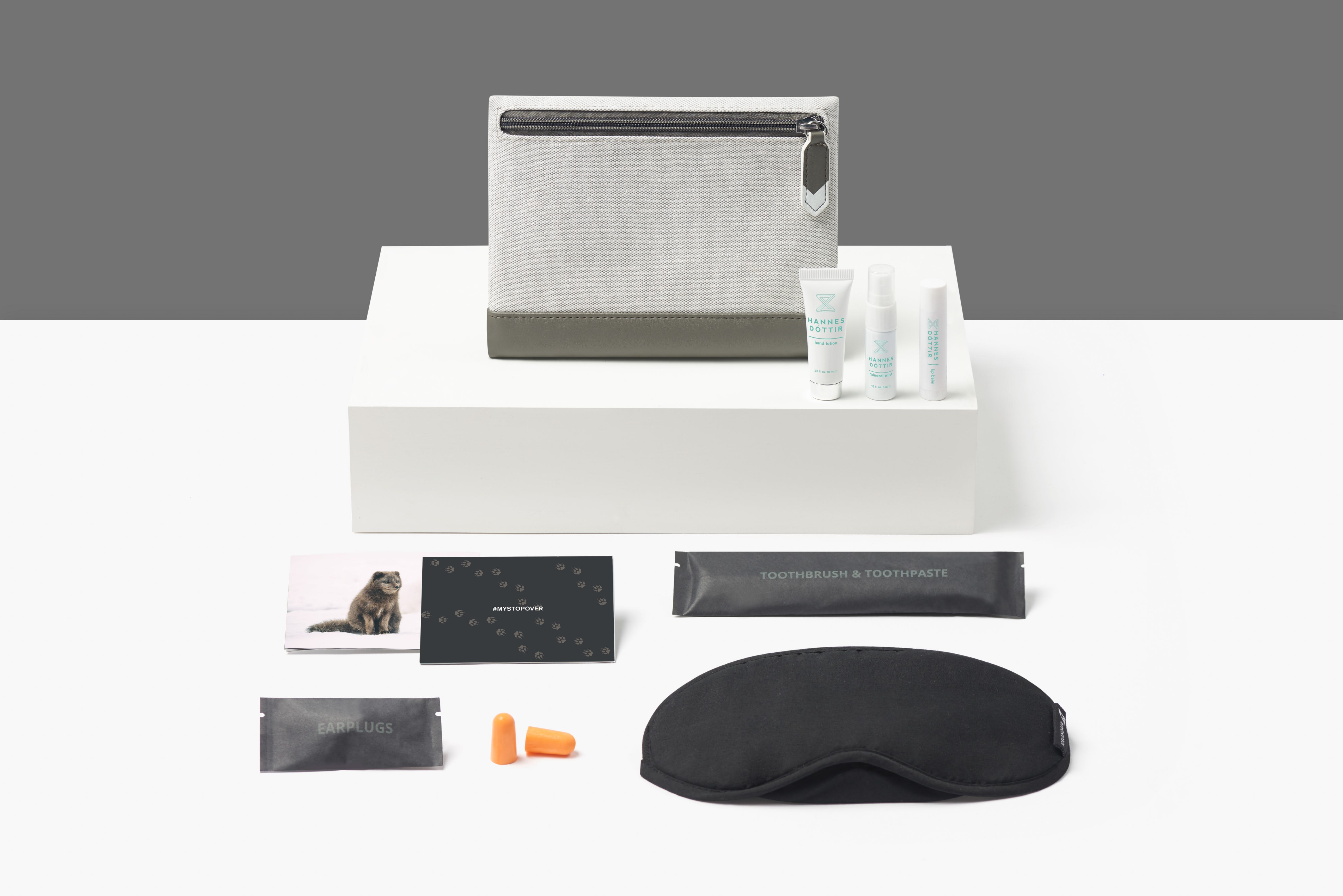 The Icelandair amenity kit displayed with all items taken out of the pouch, including an eye mask, toothbrush, toiletries and ear buds
