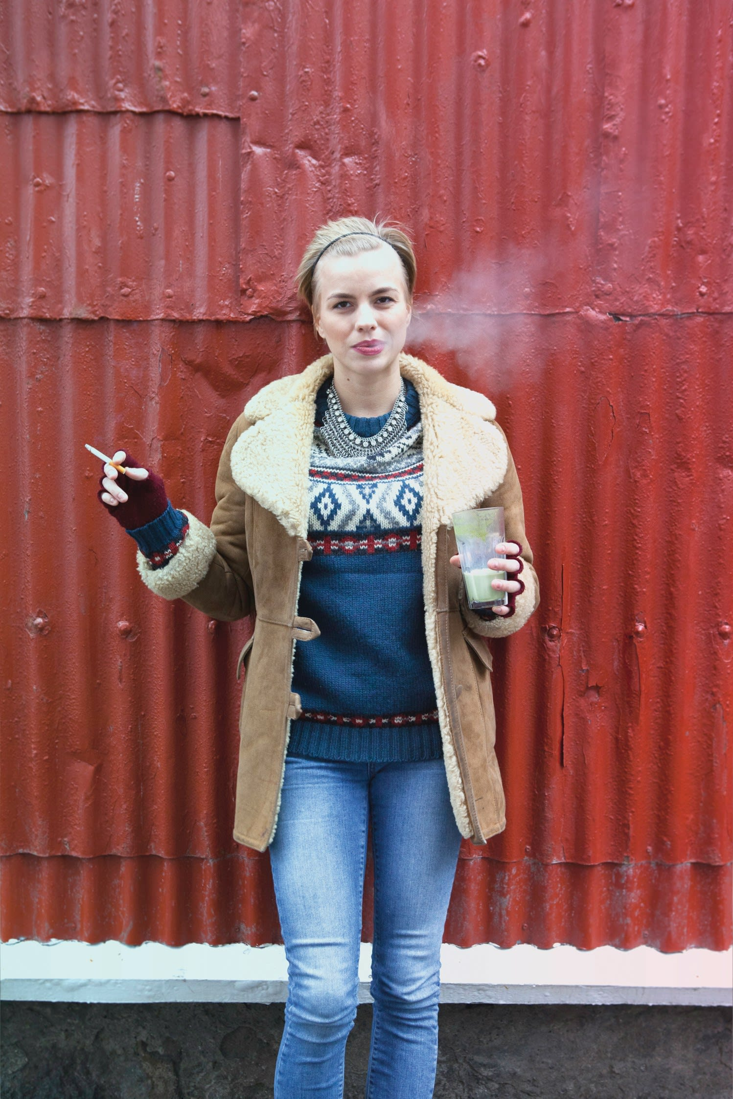 a woman standing against a red corrugated metal building wearing a blue Icelandic sweater with a green drink in one hand and a cigarette in the other