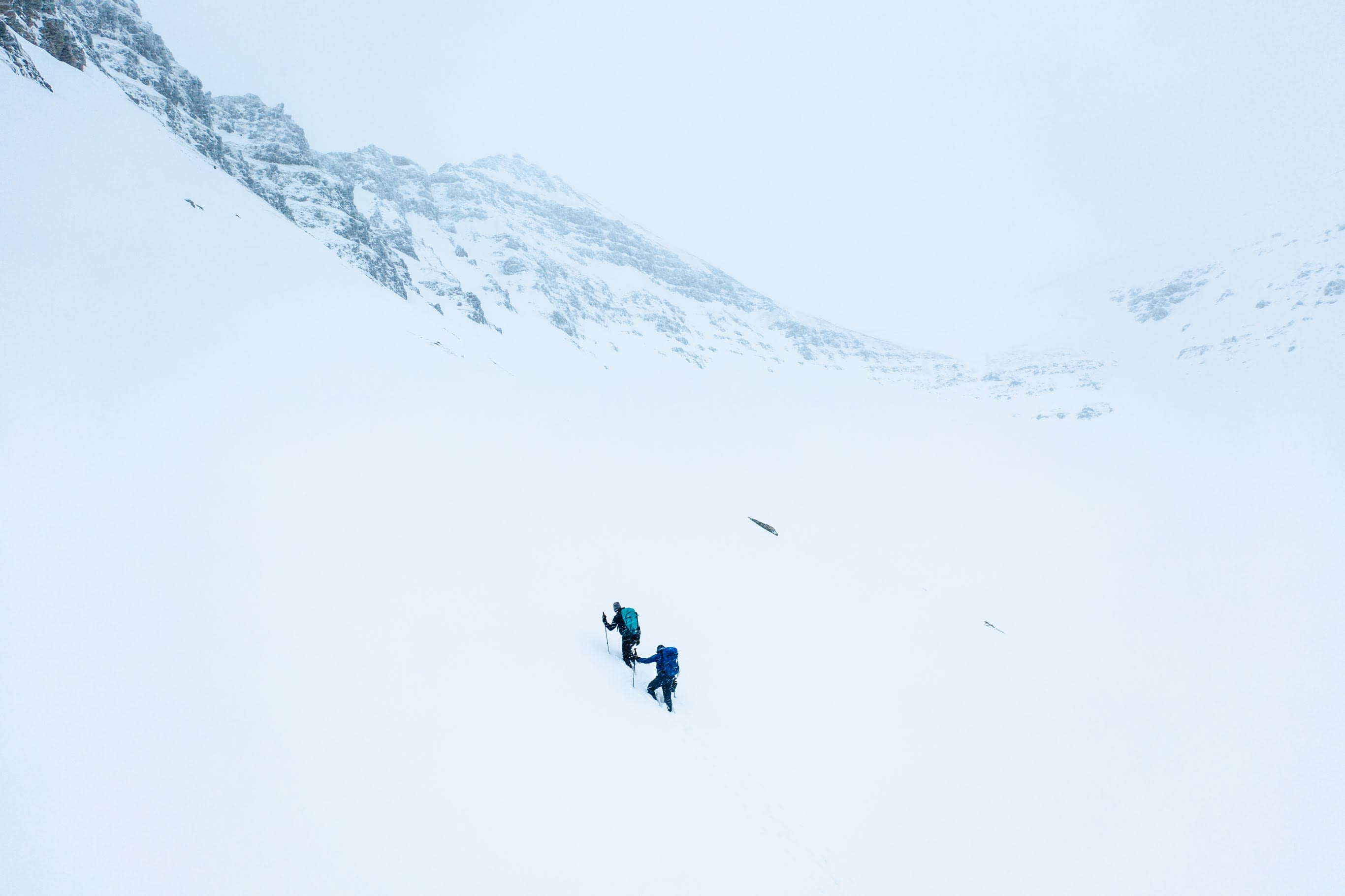two people wearing blue and black clothing hiking through a mountaineous region in Iceland