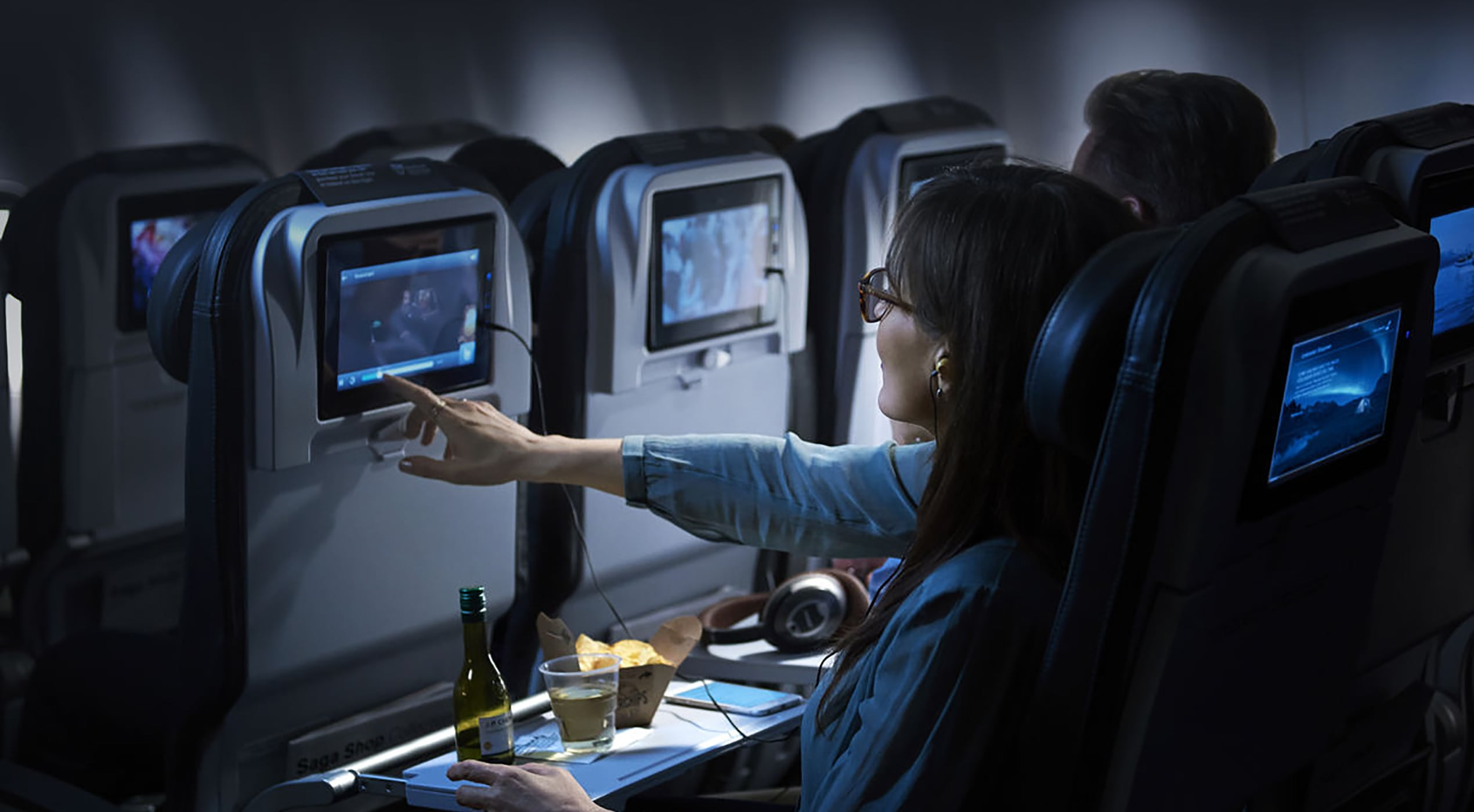 a passenger enjoying the in-flight entertainment and refreshments on board an Icelandair flight
