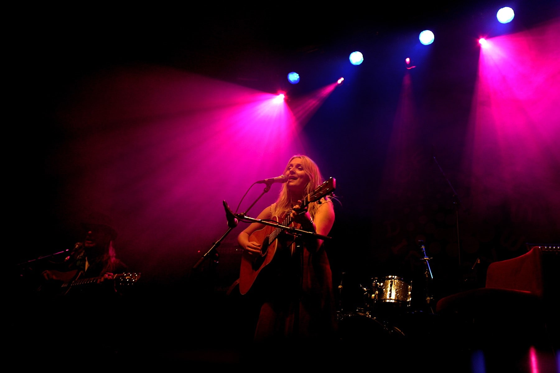Musician Eivor pictured performing on a stage with pink lighting behind