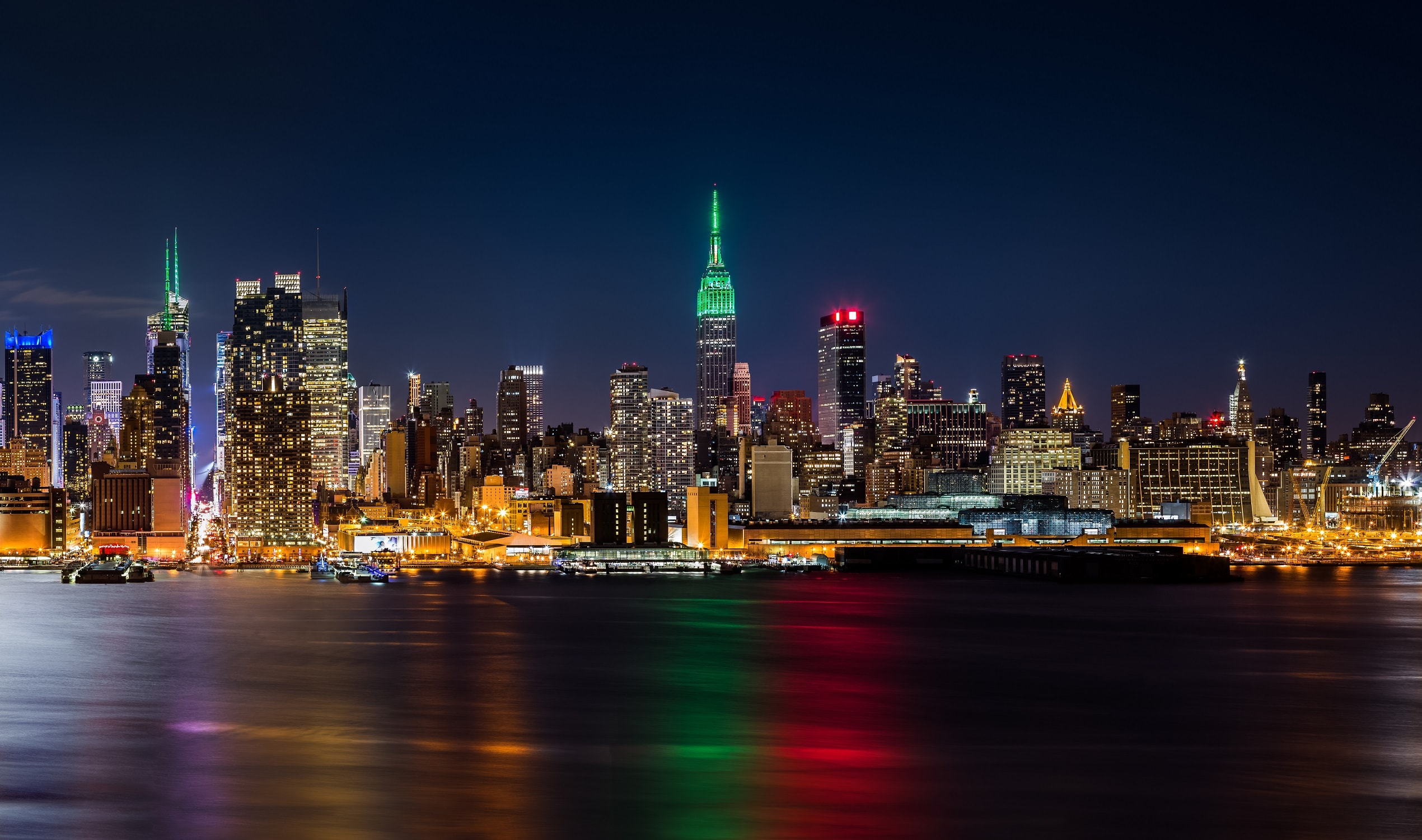 The New York city skyline viewed from the water at night, with the city lights reflecting in the water