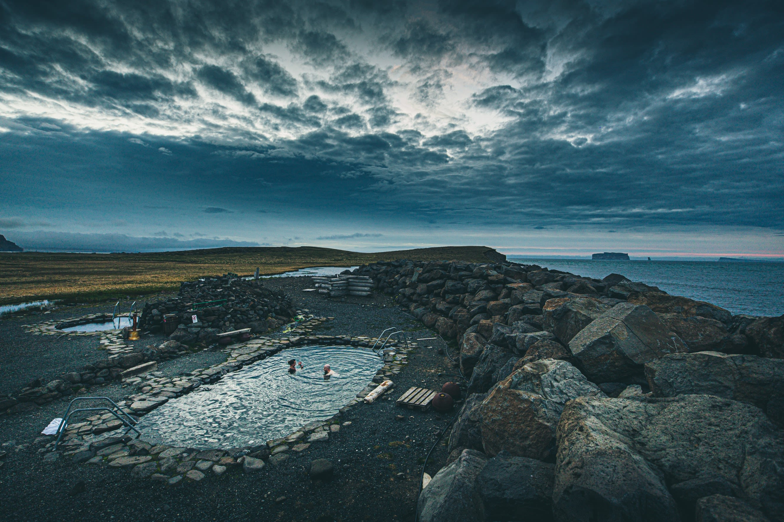An elevated view of a small outdoor pool in Iceland with views out to sea
