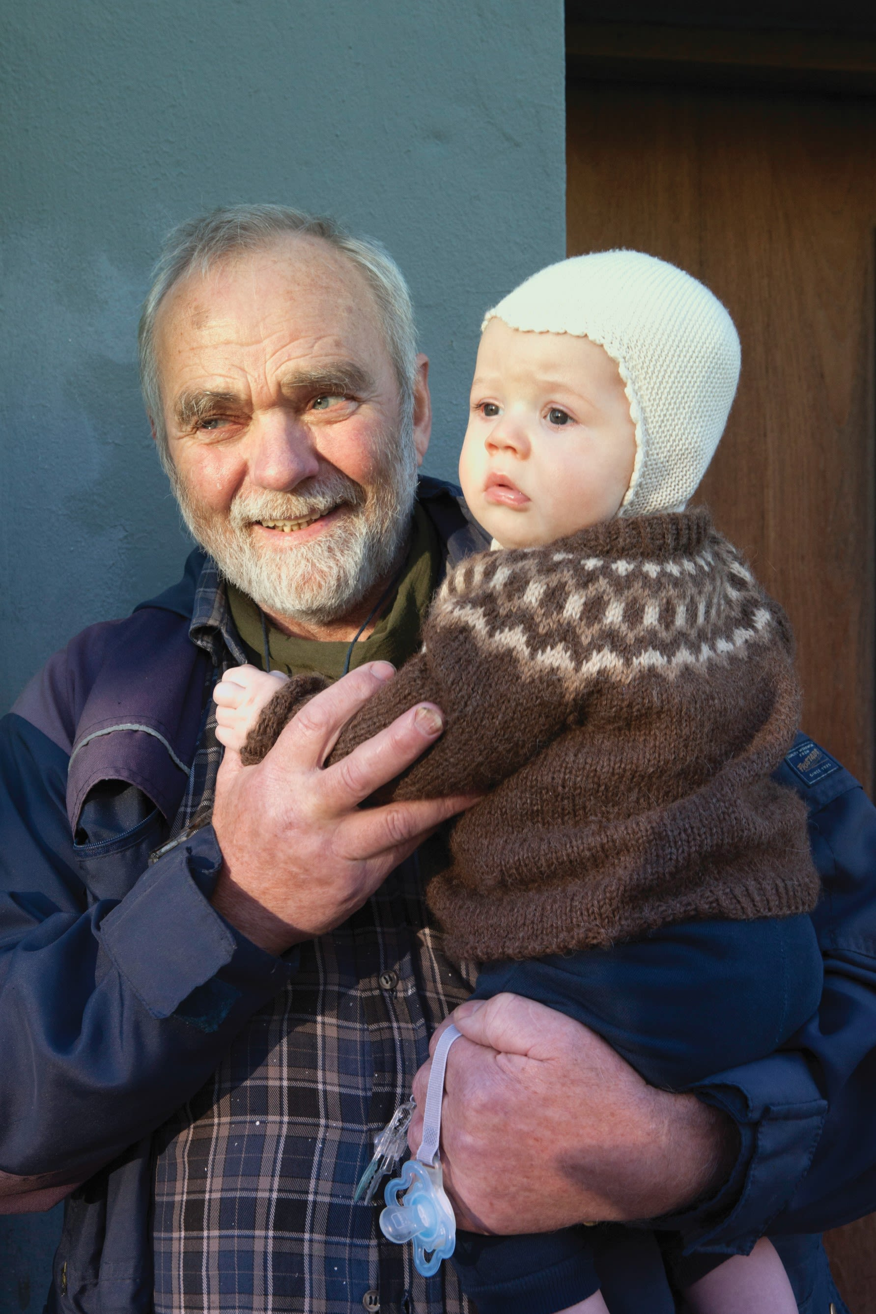 an older man holding a small baby who is wearing a brown knitted Icelandic wool sweater