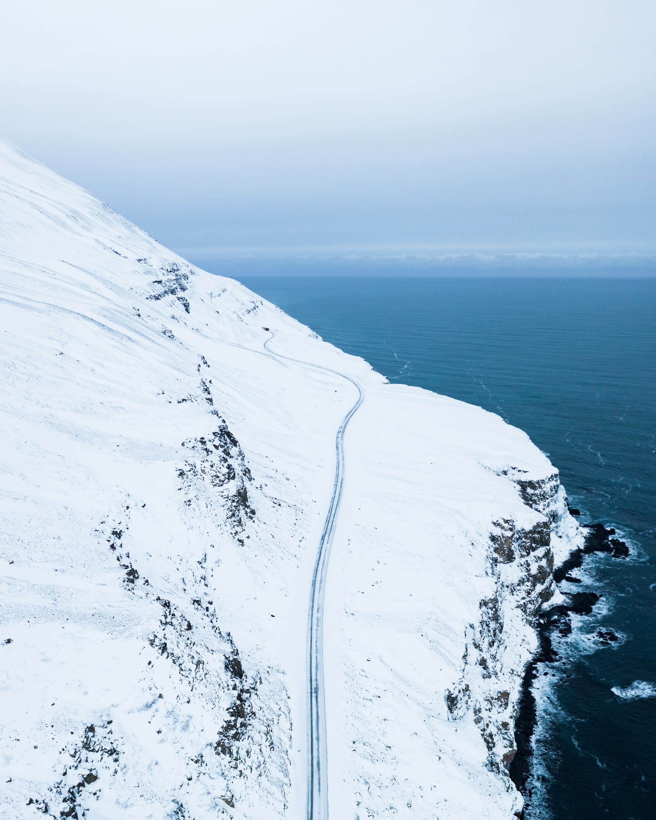 an aerial view of a fjord in Iceland with a road hugging the side of the mountain