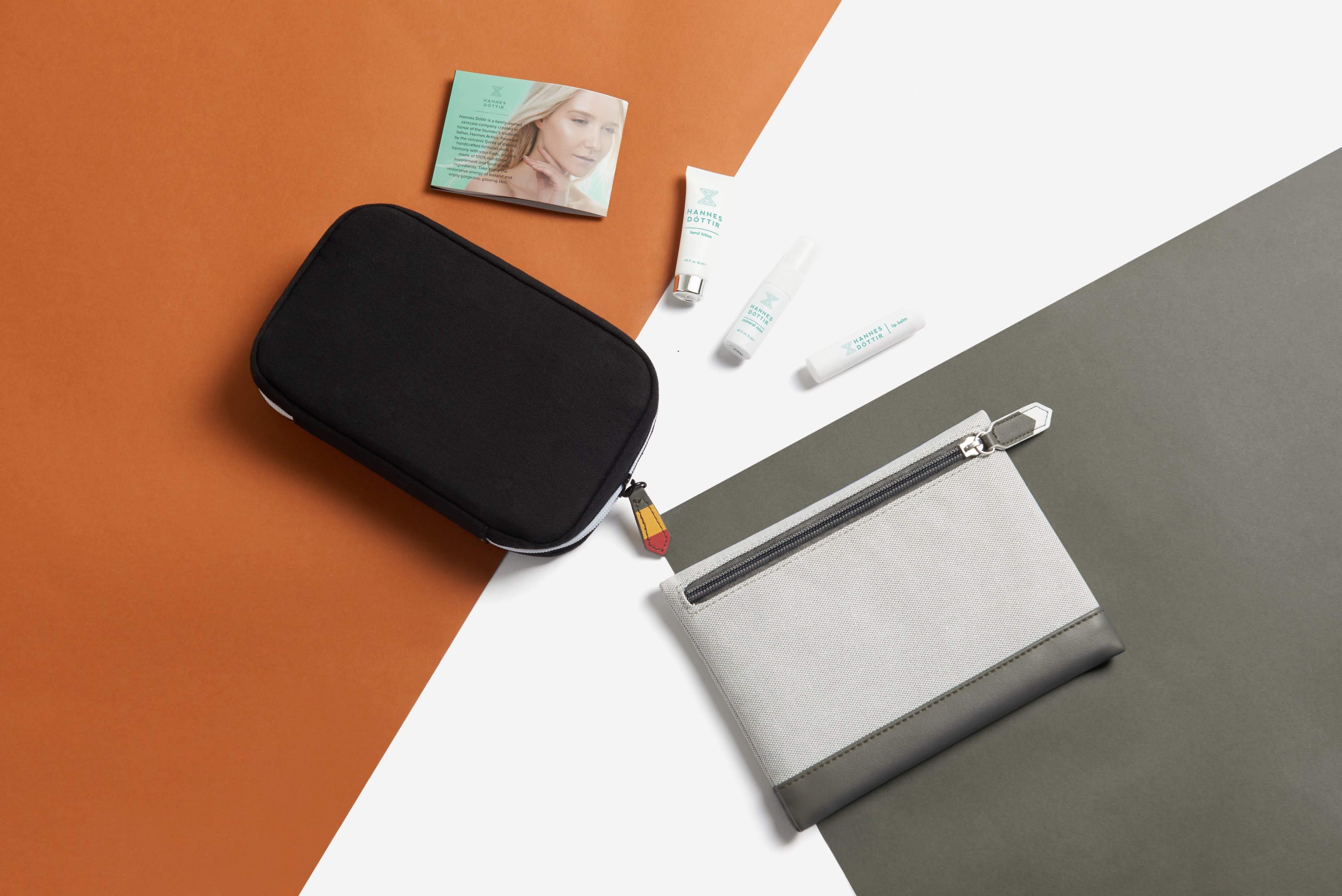 Two Icelandair amenity kit bags placed against grey, white and orange colour blocks