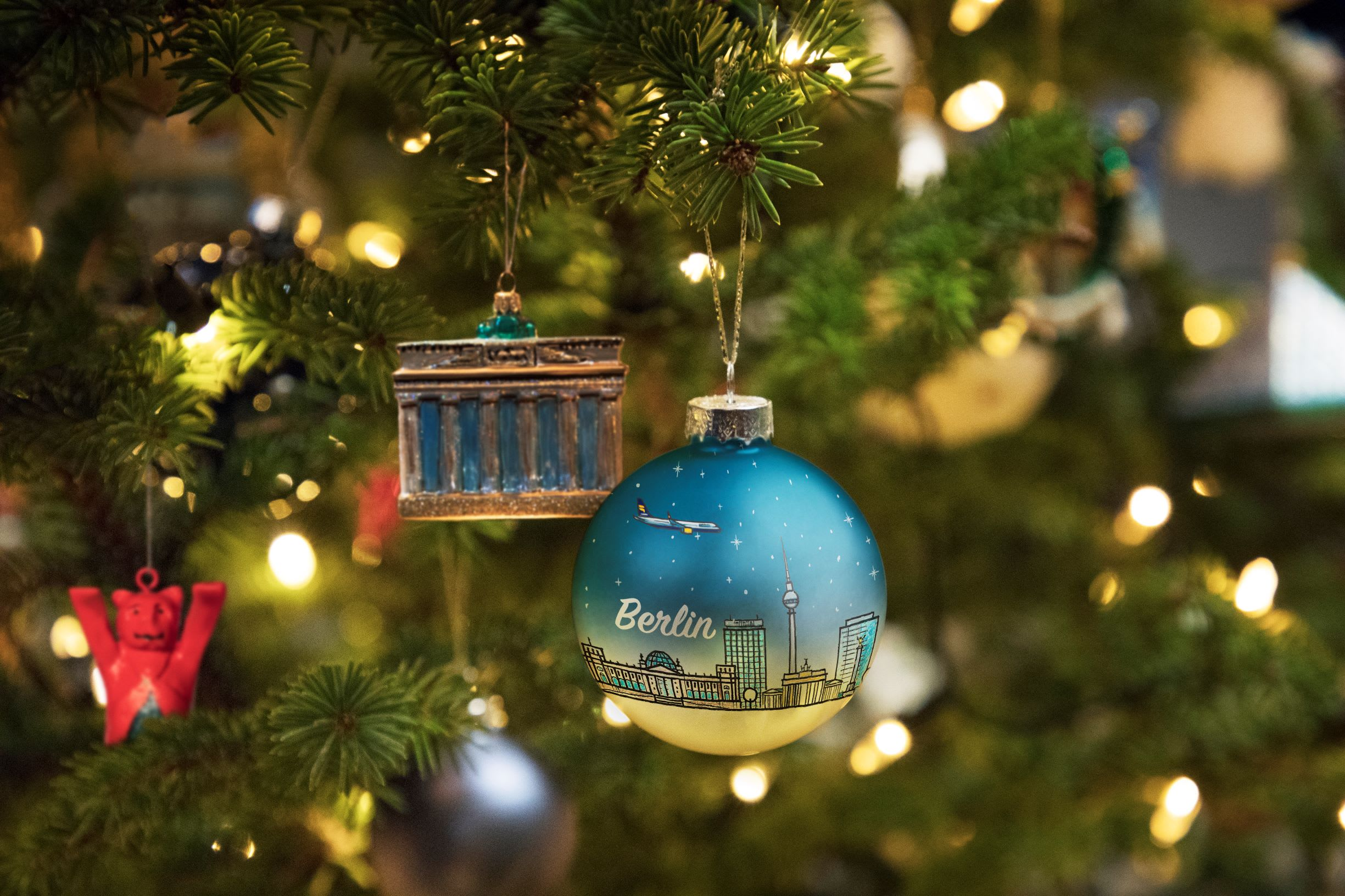 A blue bauble which reads 'Berlin' and has a city scape scene, positioned next to a decoration of the Brandenberg gate, both hanging from a green Christmas tree