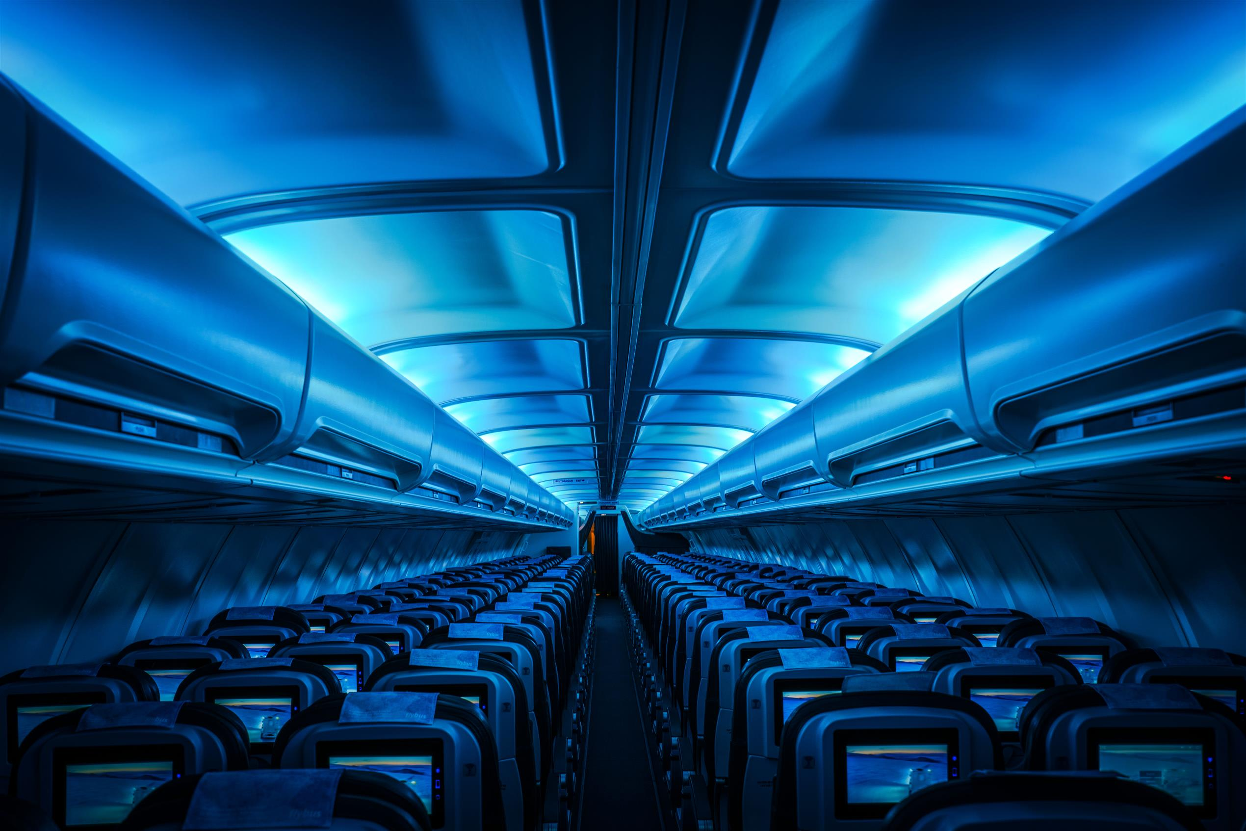 the inside of stand empty Icelandair aircraft lit up by dimmed blue overhead lights