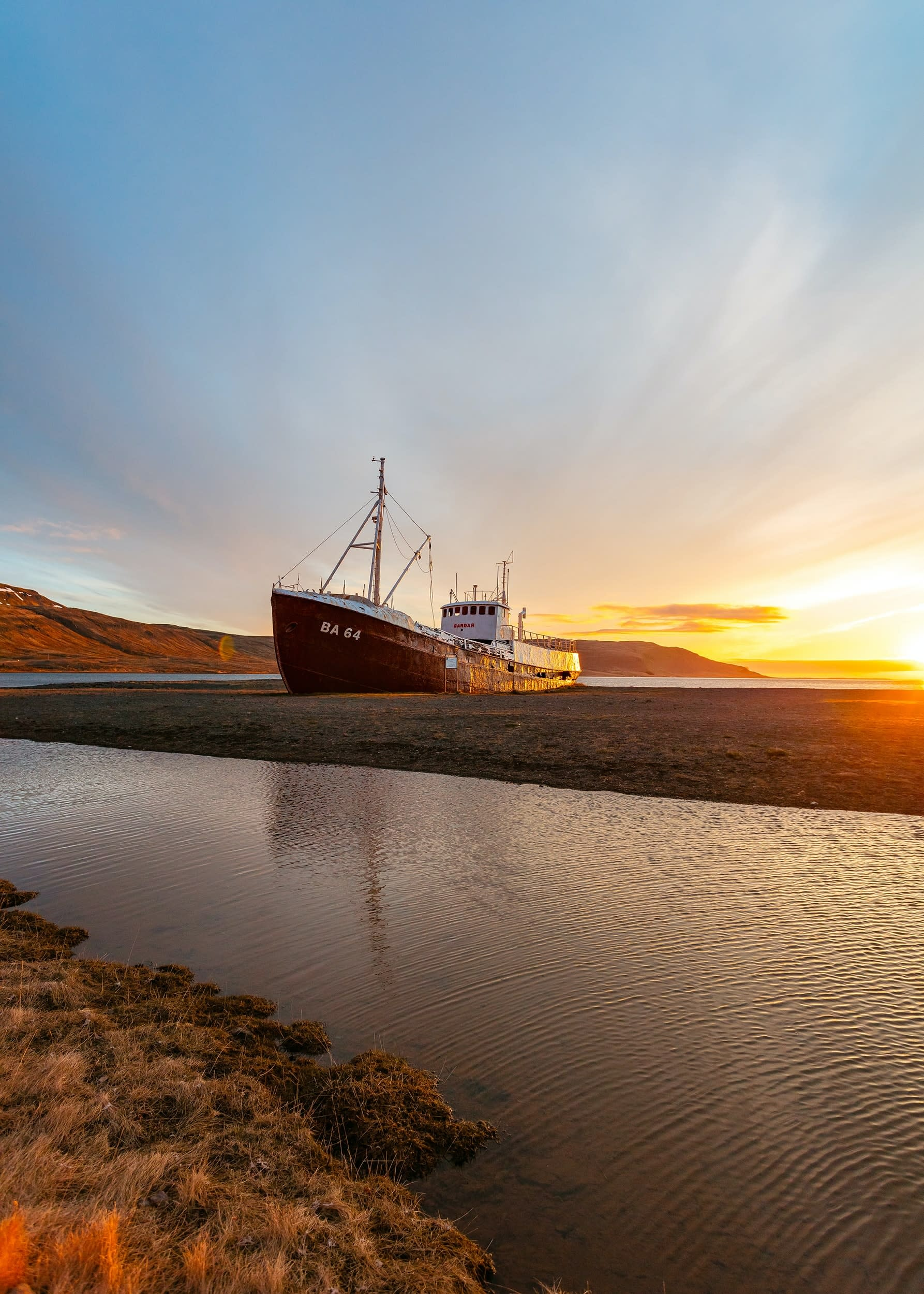 a boat - which has breached ashore in Iceland - pictured at sunset
