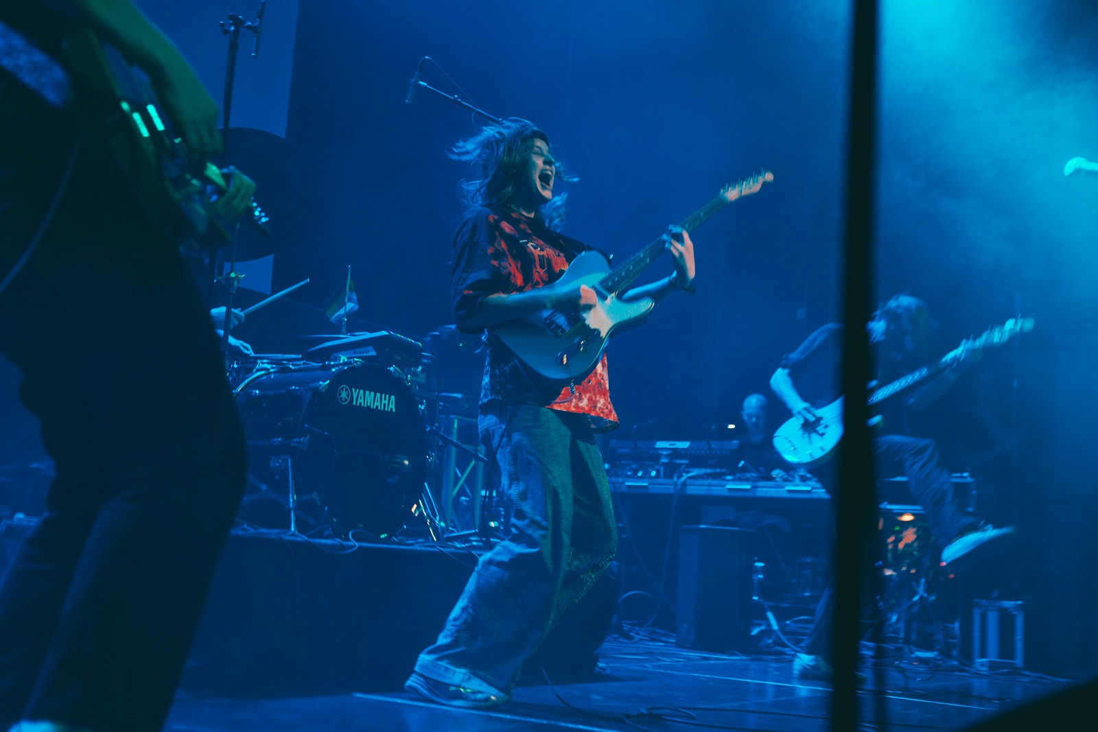 Musician Girl in Red performing with a band at Iceland Airwaves 2019, holding a guitar and looking excited