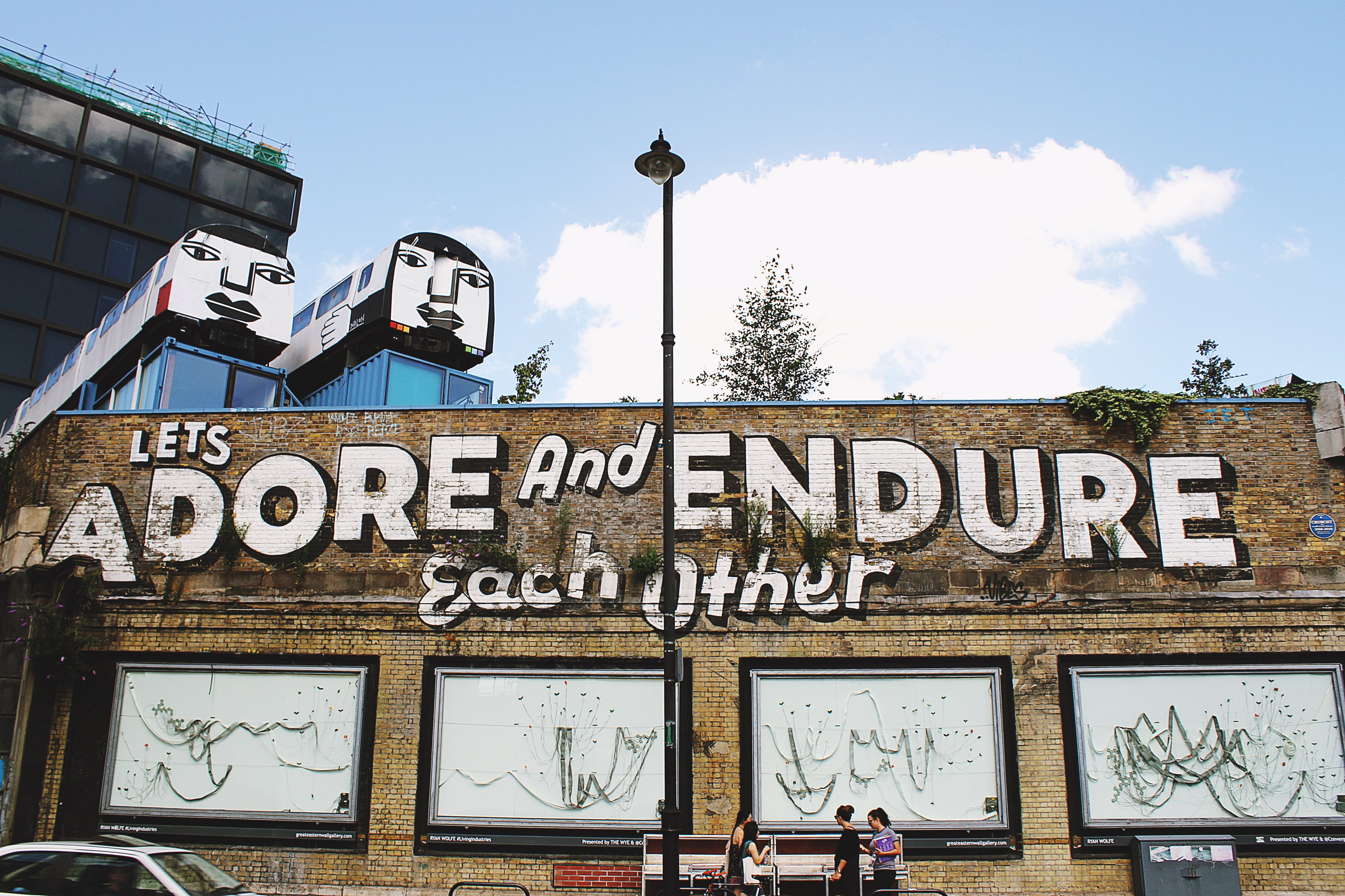 Street art in Shoreditch, painted on a brown brick wall, which reads 'Let's adore and endure each other'