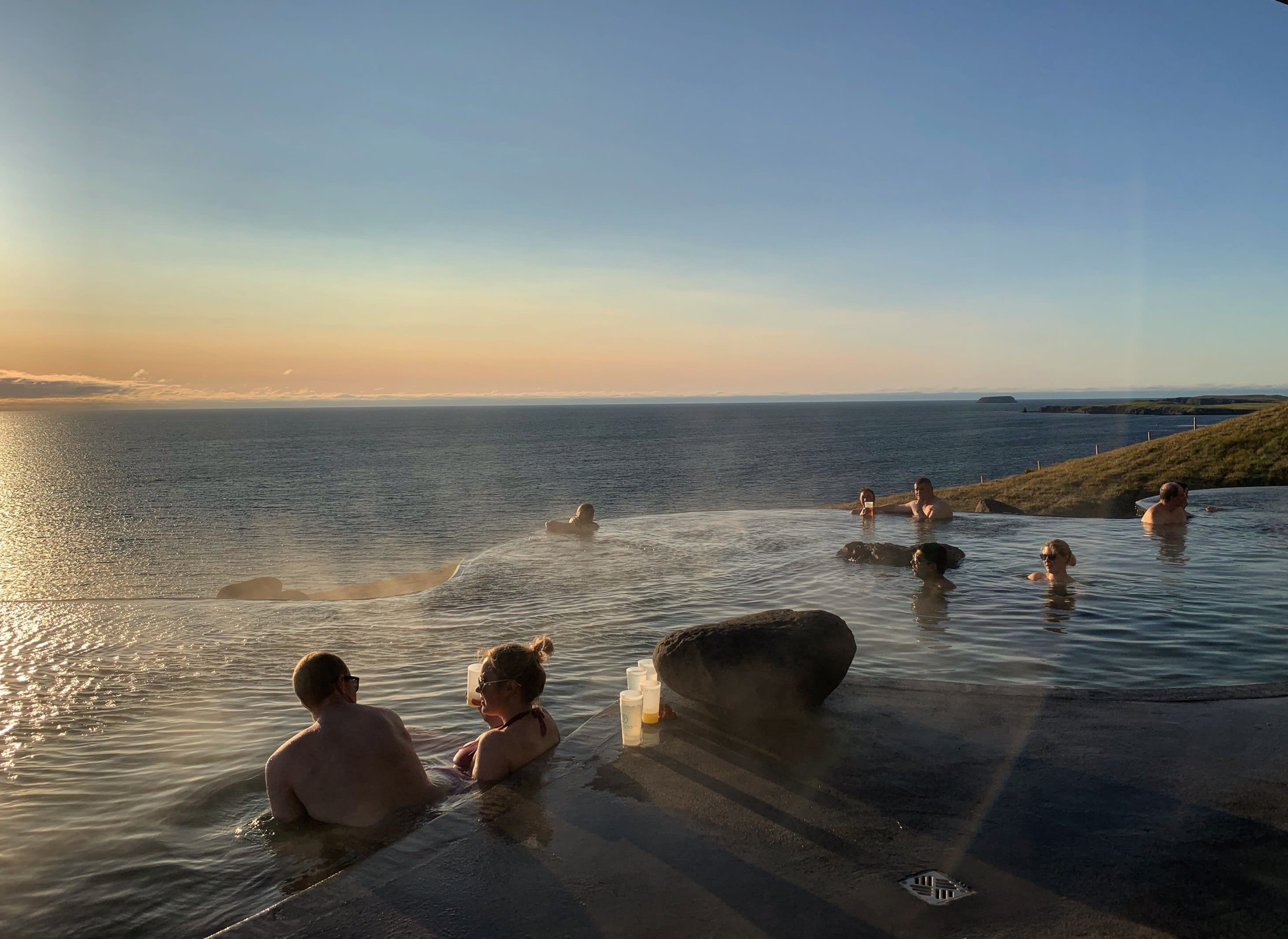 Couples gather in the warm pools at Geosea in Husavik at sunset